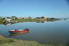 Idyllic Scene Of A Boat And Buildings Reflected in The Water On Arctic Ocean Tuk Tour In Tuktoyaktuk Northwest Territories