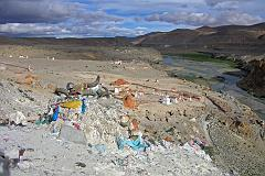 After the hot springs the trail climbs past a cremation area consecrated to Yeshe Tsogyal, and then reaches a miniature version of Kailash's Dölma La, marked with mani stones, prayer flags and a large collection of yak horns and skulls. To the left is the end of a recently constructed over 200m long mani wall, which points to the northeast directly towards Mount Kailas. The wall was the end result of a demon firing an arrow at the guru. He stopped the arrow's flight and transformed it into this wall.