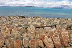 A row of mani rocks shine in one of the brief sunny breaks next to Seralung Gompa on the shores of Lake Manasarovar.